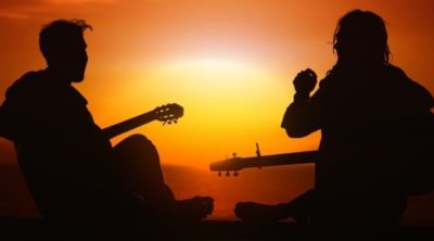 Two men in silhouette playing guitar